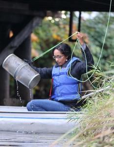 Lina Azeez pulling up a fish trap. Credit: Rick Moyer